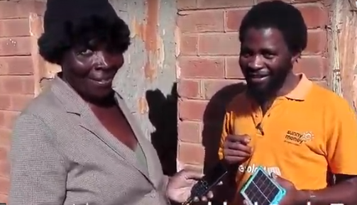 Ruth (left) uses solar for light and to charge her phone/radio. Credit SolarAid