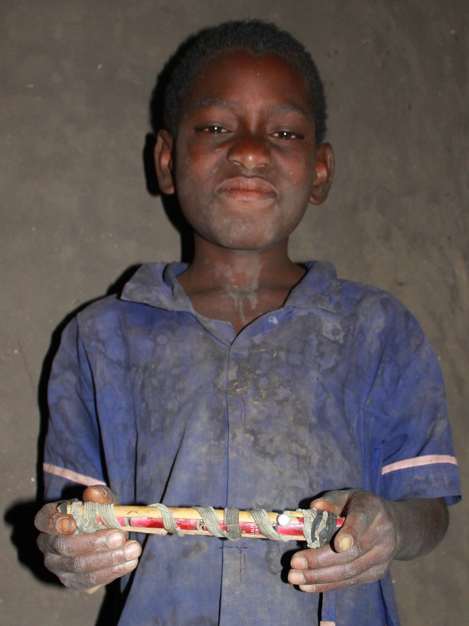 George is 9 years old. He has made a 'stick torch' which is used as the only source of lighting in his home in Malawi. It gives off less light than a candle. It's made of four batteries (three are dead ones he picked up off the ground in his village, which still have a voltage), an LED, a wire and some bark—all bound together with a shoe lace and strips of bicycle rubber. Credit: SolarAid