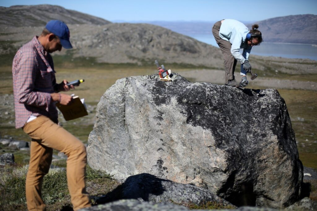 Study co-author Elizabeth Thomas, University at Buffalo assistant professor of geology, collects a sample from a boulder in Greenland. Such samples contain chemical isotopes that can help scientists determine the ancient boundaries of the ice sheet. At left is study co-author Nicolás Young, associate research professor at Columbia University's Lamont-Doherty Earth Observatory. Credit: Jason Briner